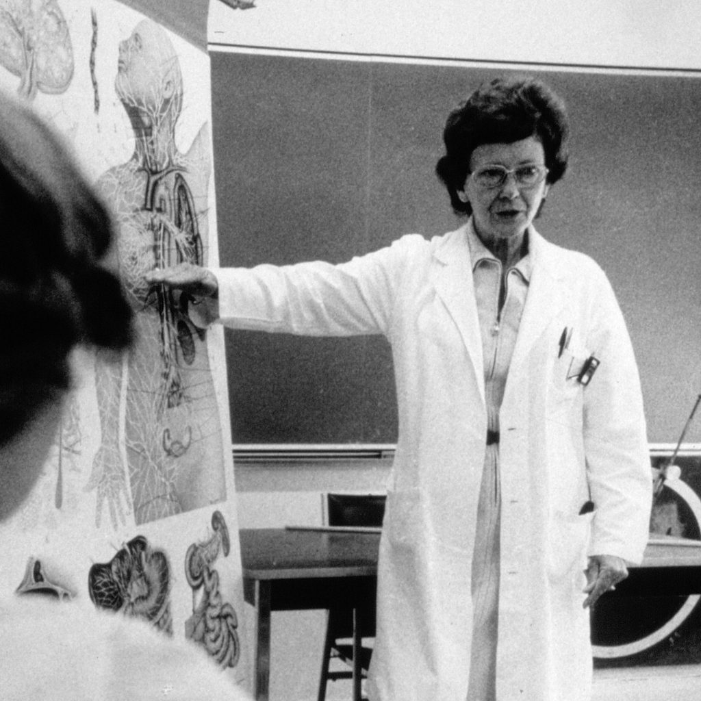 Vera Peters, in a lab coat, stands in front of a classroom and points to a flip chart featuring anatomical illustrations.
