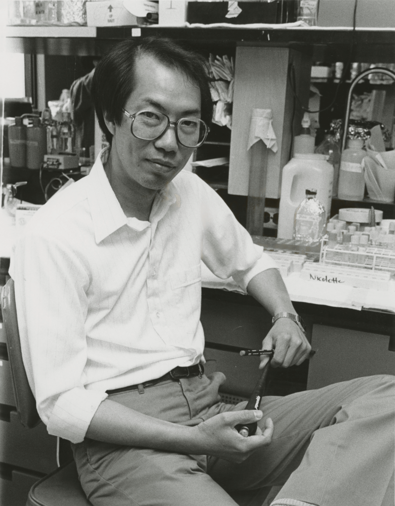 Tak Mak leans casually on a lab bench that is covered with scientific equipment.