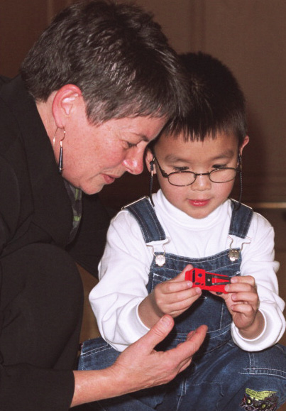 A young boy is seen playing with a toy truck with Dr. Brenda Gallie, the physician that led his treatment.