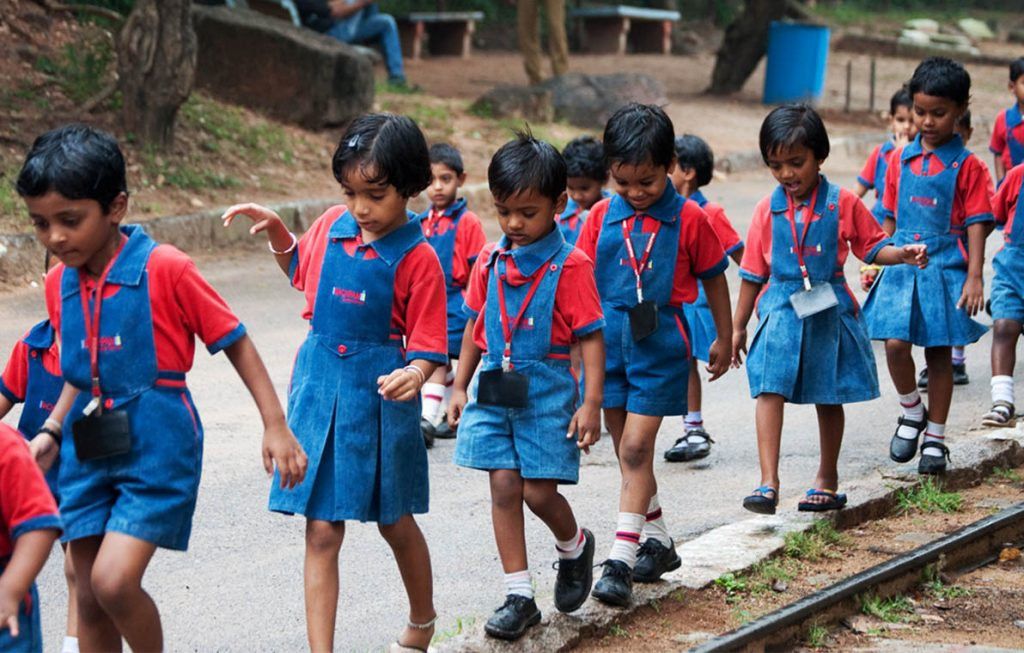 Group of young school children in India. They are dressed in red and blue uniforms and are walking in a line on a paved road.