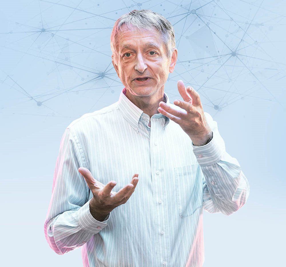 Geoffrey Hinton gestures while talking. Behind him is a drawing of a network of lines joined by many nodes.