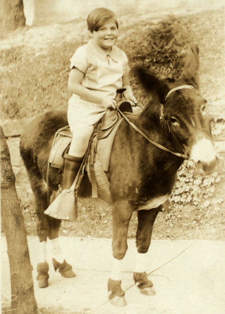 A postcard showing Janet Turnbull smiling as she sits on a donkey. A handwritten message reads in part: I am feeling fine.