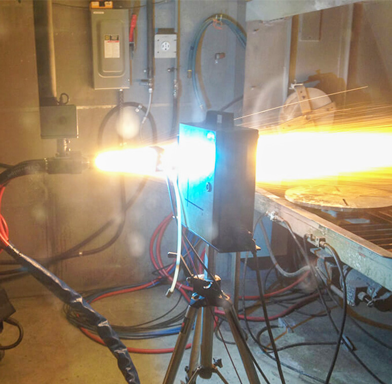 In a lab, a jet of something bright and hot shoots out of a hose and through a metal box.