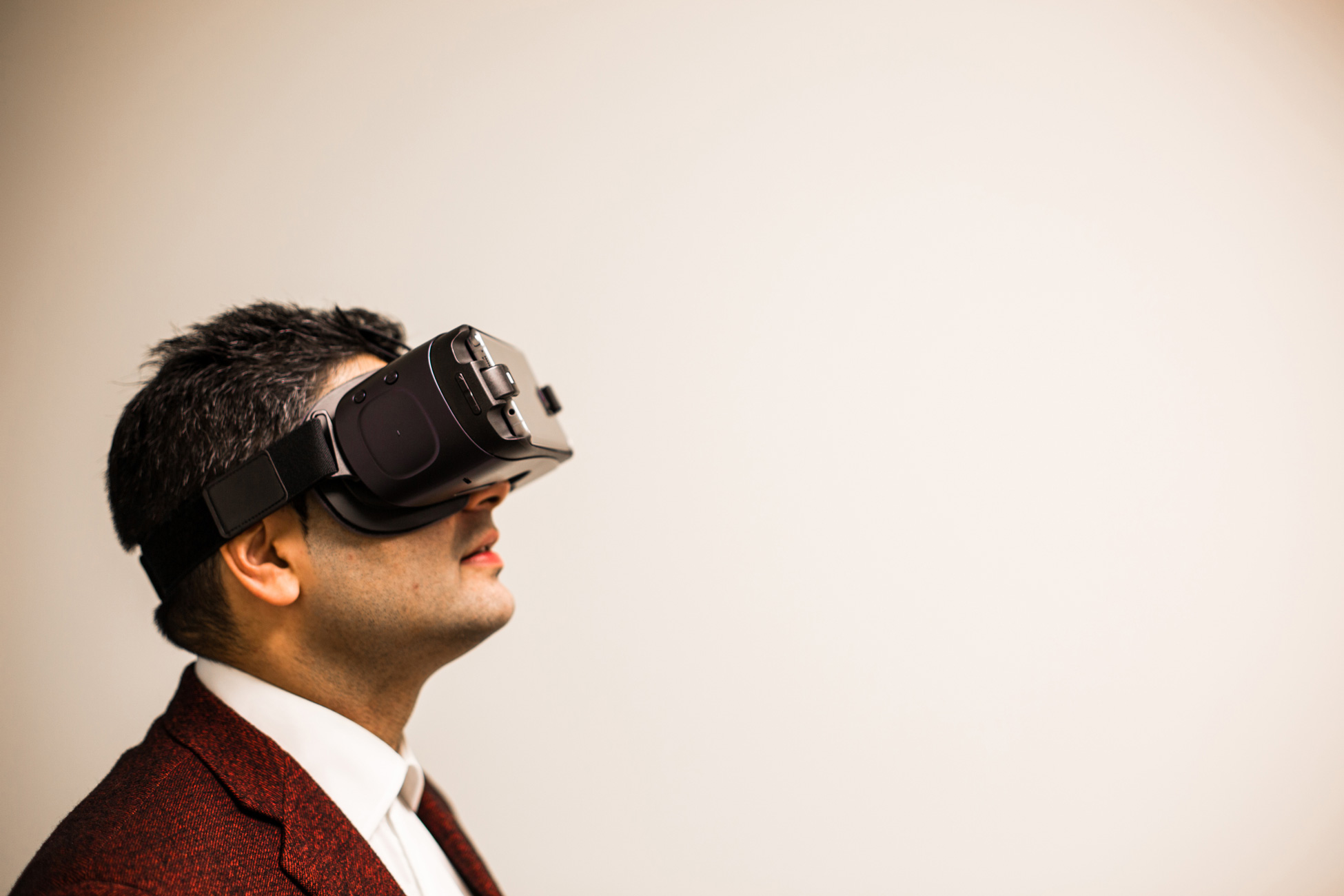 A man wearing a virtual reality headset looks up.
