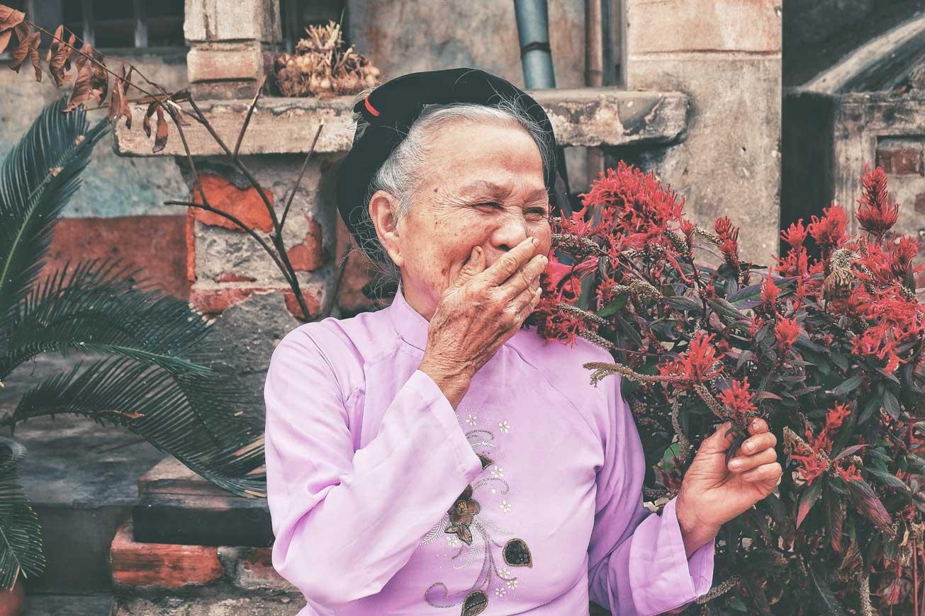 A happy elderly woman standing in a flower garden.