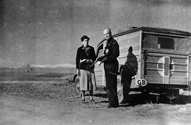A woman and a uniformed man who is likely Norman Bethune stand in a desert beside a truck painted with the Red Cross symbol.