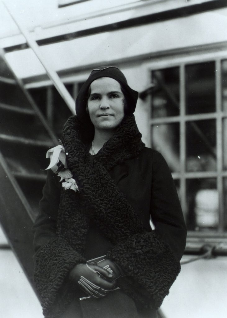 In December 1930, a healthy-looking Elizabeth Hughes wears fashionable clothes and stands on the deck of a passenger ship.