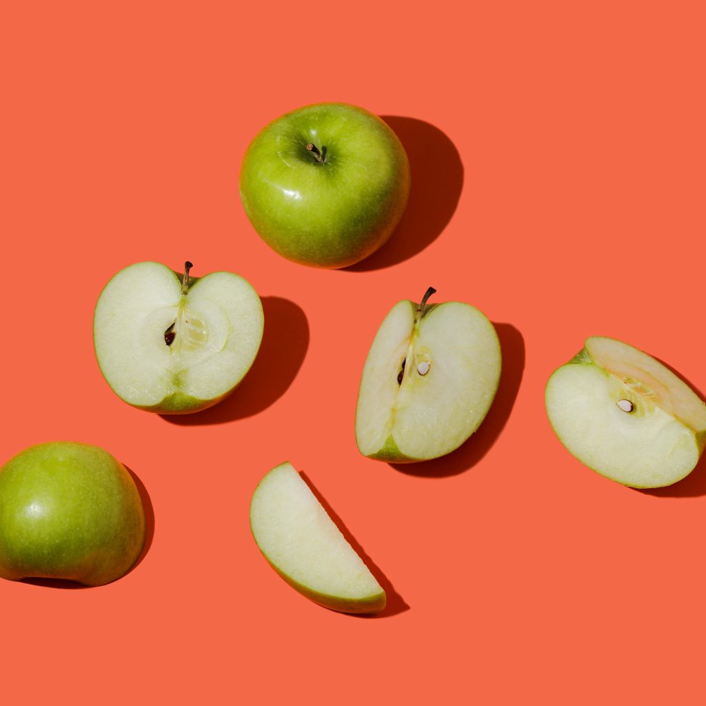 A whole granny smith apple and some apple slices sit on a salmon-coloured background.