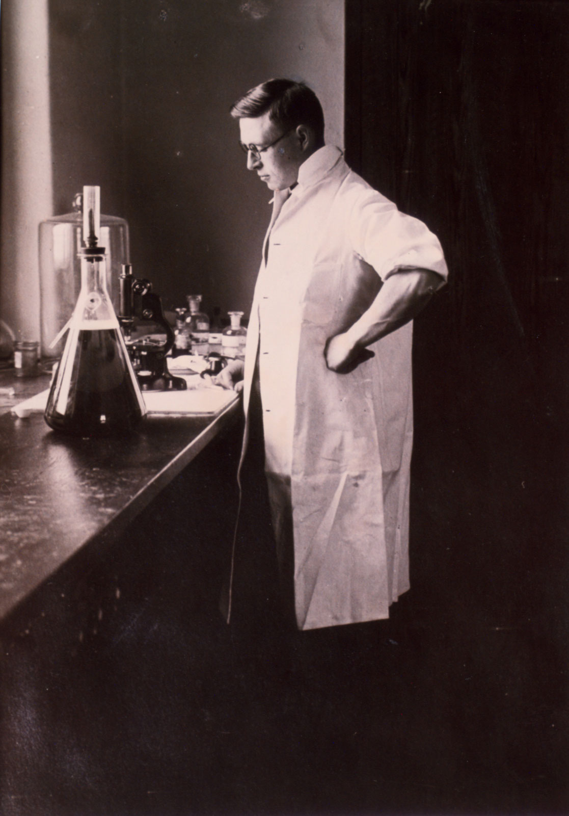 A young James B. Collip wears a lab coat and glasses. He stands in front of a lab bench containing a microscope and glassware.