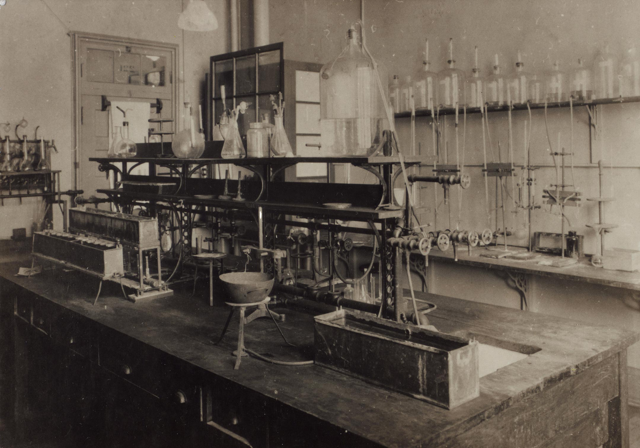 The lab where insulin was discovered: a wooden workbench filled with instruments, and a wall lined with bottles and tubing.