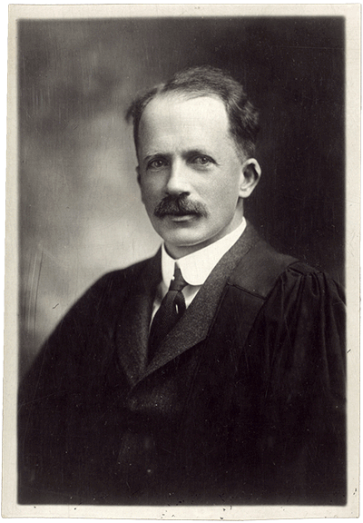 A black and white head and shoulders portrait of J. J. R. Macleod in academic dress.