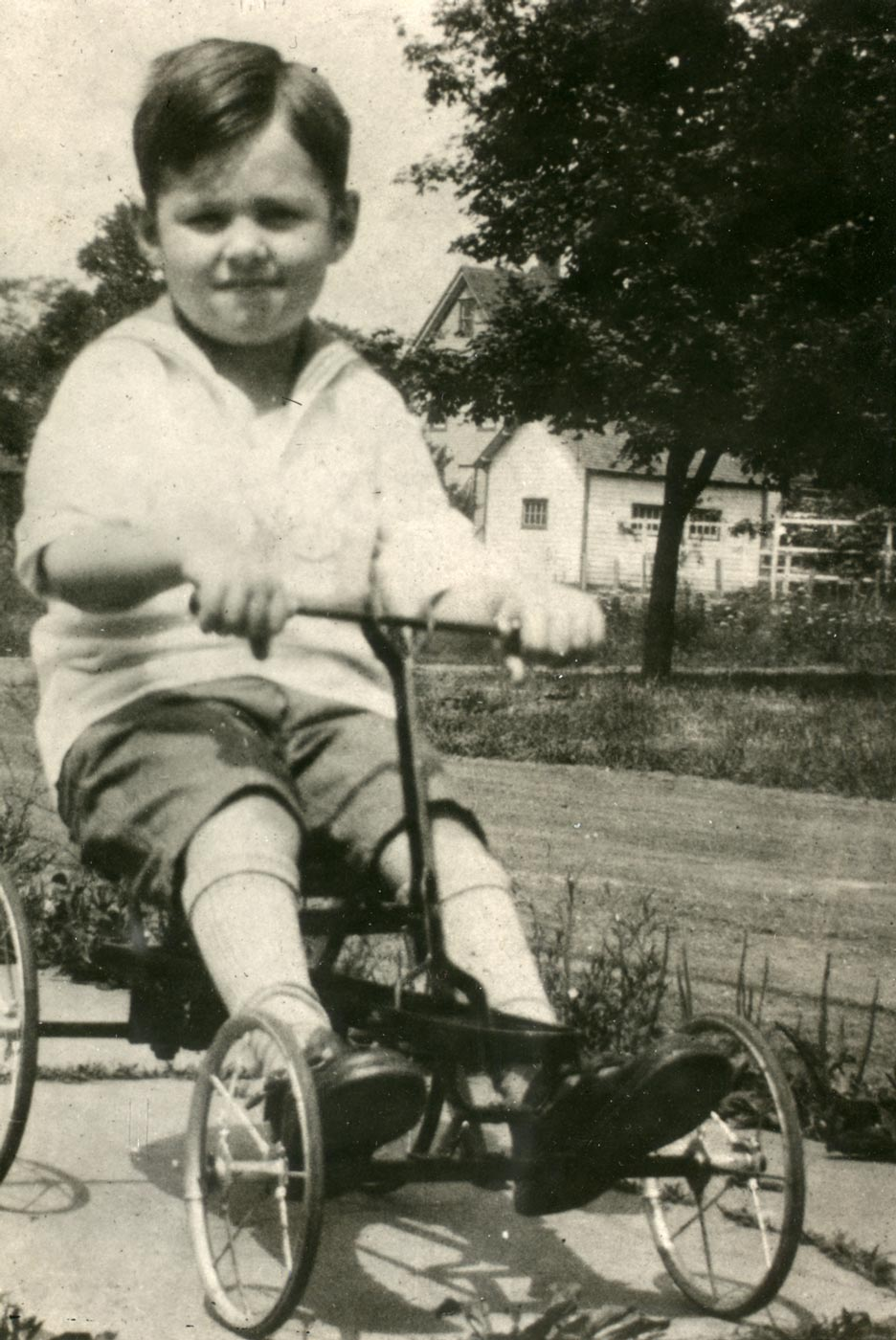 A black and white photograph of a healthy Teddy Ryder riding a tricycle.
