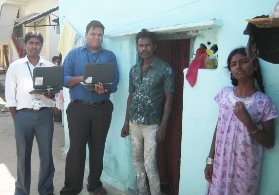 A group of researchers (two holding laptops) stand ouside of the front door of a house.