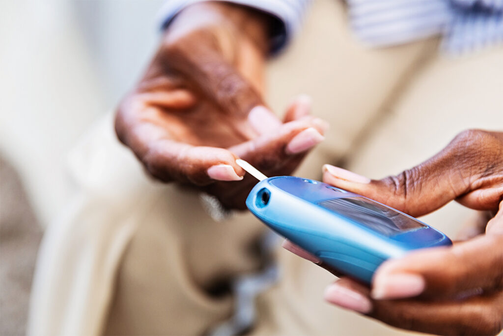 A woman pricks her finger with a palm-sized device for measuring blood sugar levels.