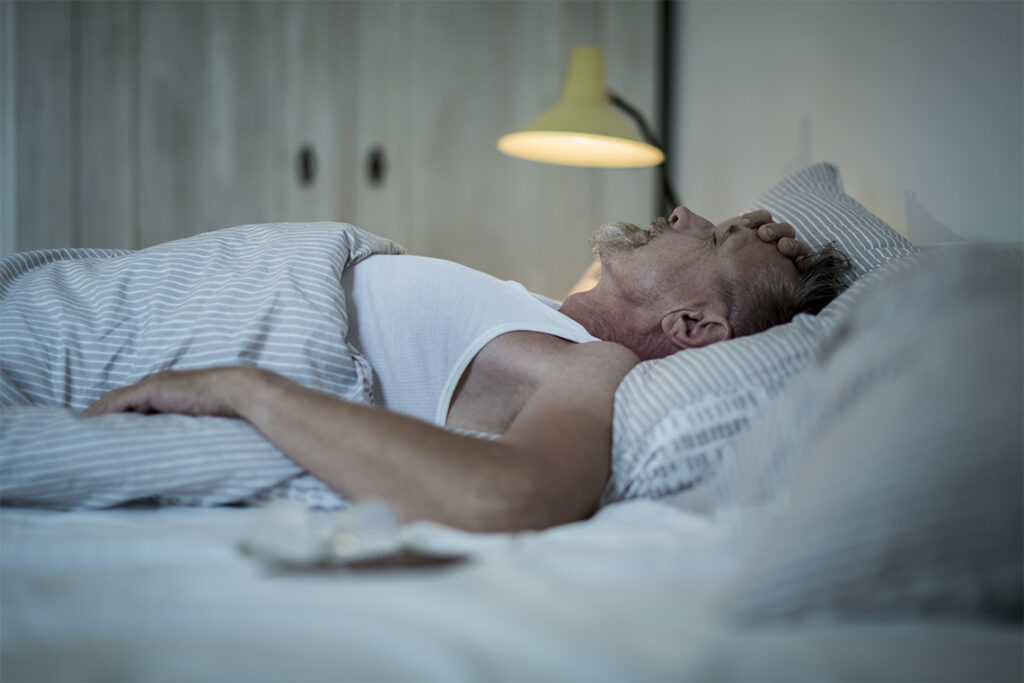 An older man lies on his back in bed with his hand clapped to his forehead, and the light on.