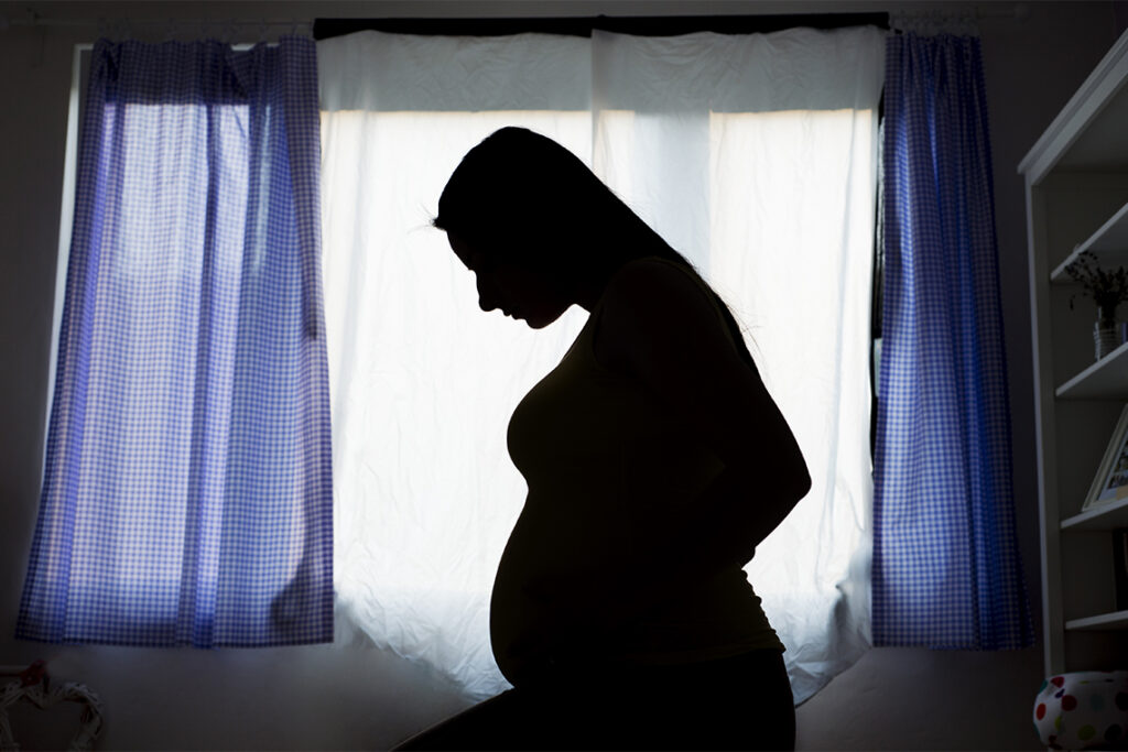 A pregnant woman, looking down at her belly, is silhouetted against a curtained window.