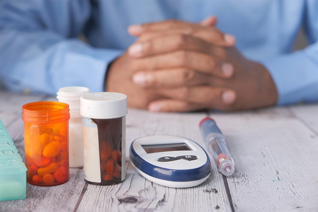A doctor sits beside a blood sugar metre and other diabetes medications